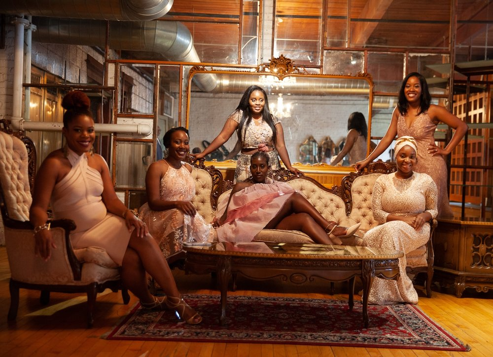 Bridal party sits on vintage couches