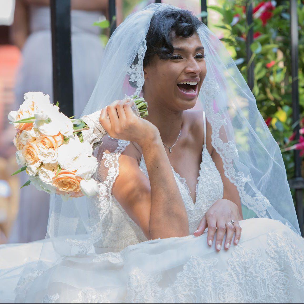 Bride laughs holding bouquet