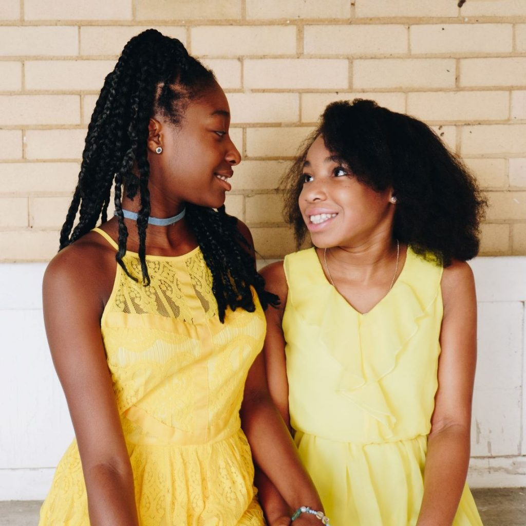 Two girls in yellow dresses chat on bench