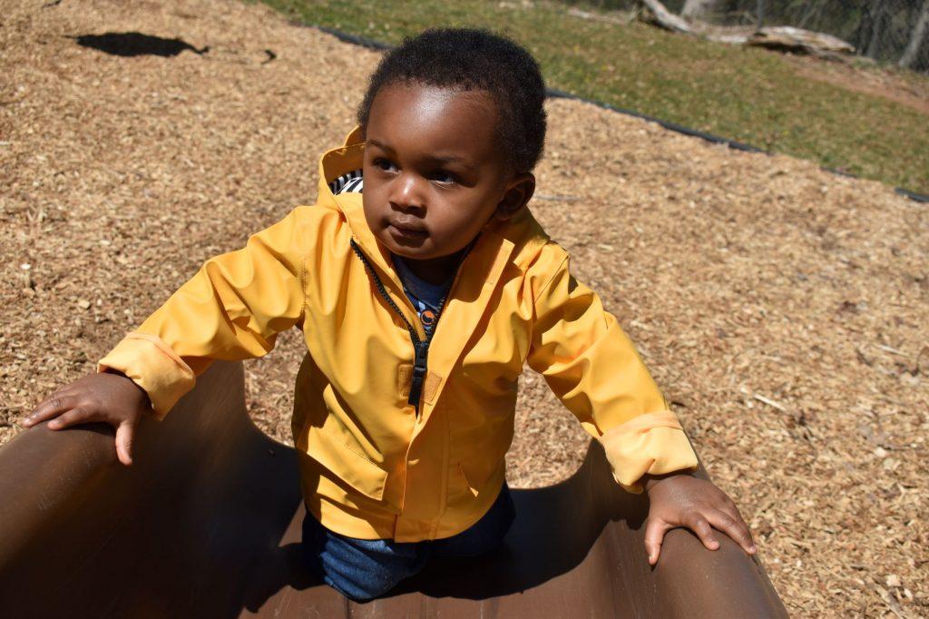 Boy in yellow rain coat climbs slide